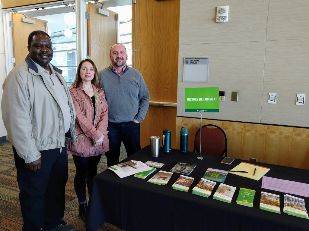 Three faculty members standing by the History table with pamphlets.